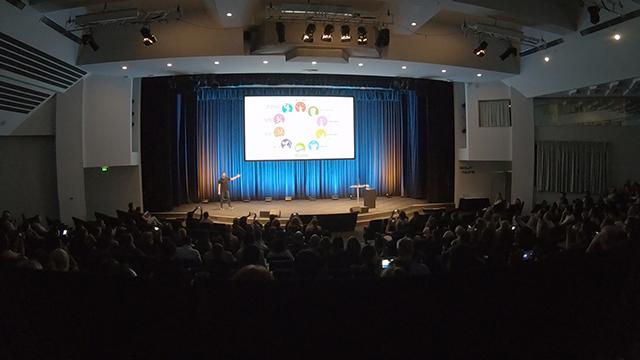 Josh Stinton föreläser på scen inför publik
